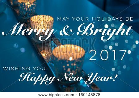 """Merry and Bright Christmas holiday winter season greeting card with candles burning and sparking light reflections with seasons greetings """"may your holidays be merry & bright"""" and """"happy new year 2017"""" written on card"""