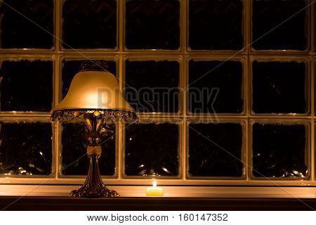 A candle lit lamp casting a golden glow against a frosted multi square paned window