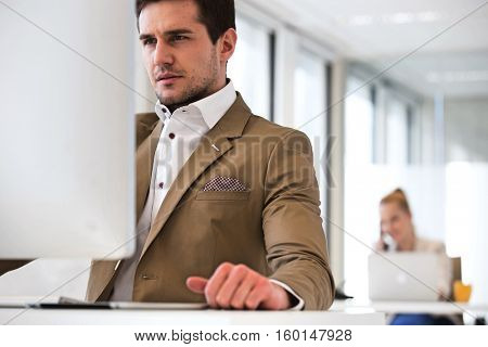 Handsome young businessman using computer in office with female colleague in background