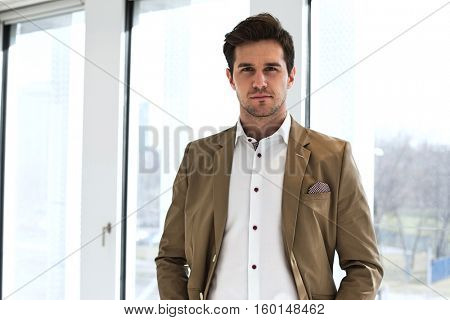 Portrait of confident young businessman standing against office window
