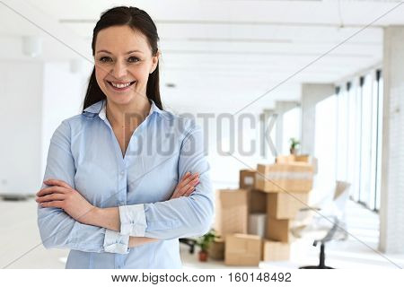 Portrait of smiling mid adult businesswoman standing arms crossed in new office
