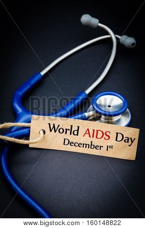 World AIDS day December 1st in paper tag with stethoscope on black background - health concept. Medical conceptual
