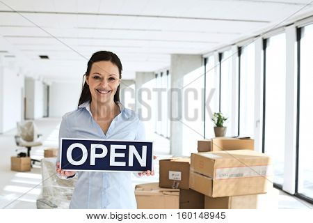 Portrait of smiling businesswoman holding open sign in new office
