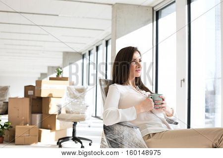 Thoughtful young businesswoman having coffee in new office