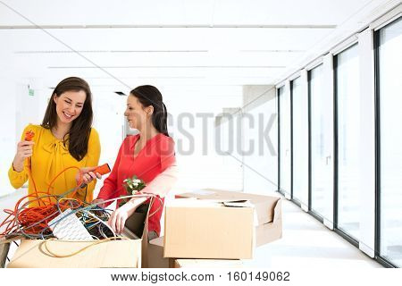 Businesswomen untangling cords while standing by cardboard boxes in new office
