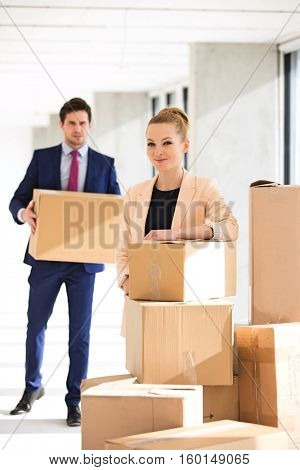 Portrait of confident young businesswoman standing by stacked boxes with male colleague in background at office