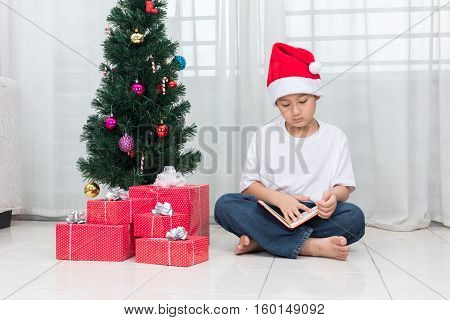 Asian Chinese Little Boy Reading Book Beside Christmas Presents