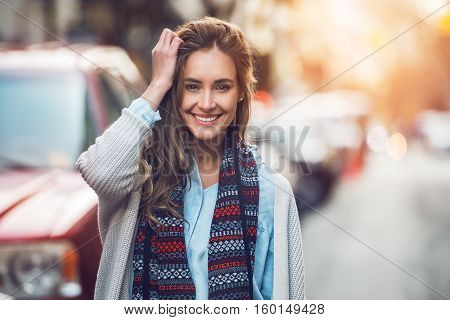 Happy young adult woman smiling with teeth smile outdoors and walking on city street at sunset time weating winter clothes and knitted scarf.