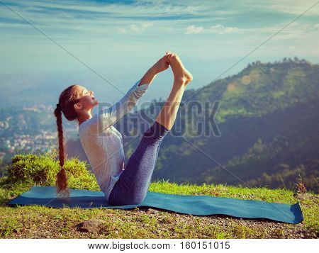 Yoga outdoors - woman doing Ashtanga Vinyasa Yoga balance asana Ubhaya padangusthasana Big Double Toe Yoga Pose in Himalayas in India in the morning. Vintage retro effect filtered hipster style image.