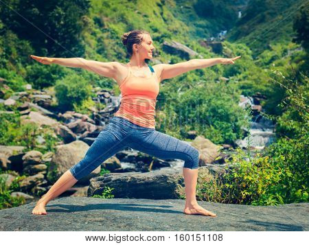 Yoga outdoors - sporty fit woman doing Ashtanga Vinyasa Yoga asana Virabhadrasana 2 Warrior pose posture at tropical waterfall. Vintage retro effect filtered hipster style image.
