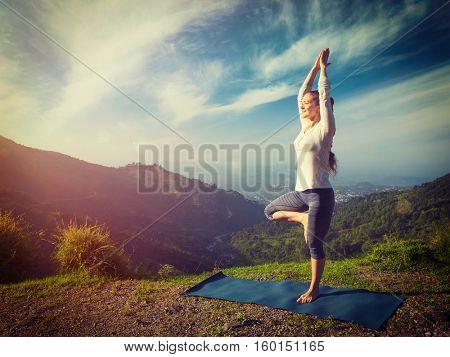 Yoga practice outdoors - woman practices balance yoga asana Vrikshasana tree pose in Himalayas mountains outdoors in the morning. Himachal Pradesh, India. Vintage retro filtered hipster style image.
