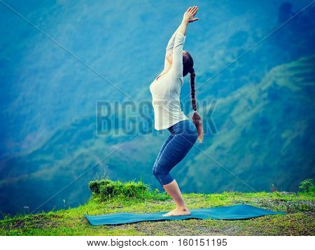 Young sporty fit woman doing yoga asana Utkatasana (chair pose) outdoors in mountains Himalayas in India. Vintage retro effect filtered hipster style image.