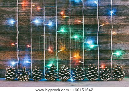 festive wooden background from old boards with garland and firry cones. with space for text. the concept of a new year Christmas. tinted photo