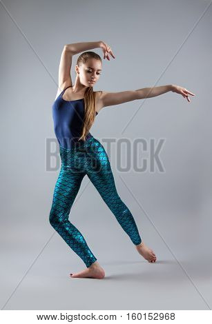 Young Beautiful Girl Dancing. Woman In A Blue T-shirt And Blue Tights.