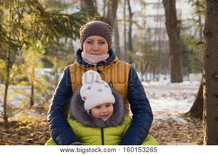 Happy family: a young woman with her little cute daughter in the winter november city park, horizontal