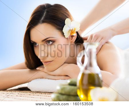 Beautiful, young and healthy woman in spa salon. Massage treatment, traditional medicine and healing concept. Blue background.