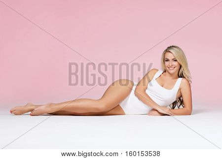 Fit and sporty girl over pink colored background. Sport, fitness, diet, weight loss and healthcare concept.