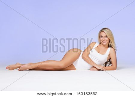 Fit and sporty girl posing over blue background. Sport, fitness, diet, weight loss and healthcare concept.
