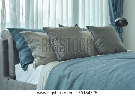 Gray And Deep Blue Pillows Setting On Bed In Deep Blue Color Scheme Bedding