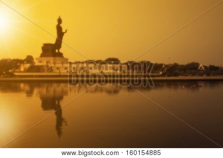 soft filter beautiful landscape silhouette buddha statue sacred with sunset and reflection shadow on the lake and clear sky at phutthamonthon in Thailand