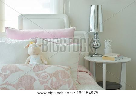 Pink And White Pillows On Bed With Chrome Finished Table Lamp