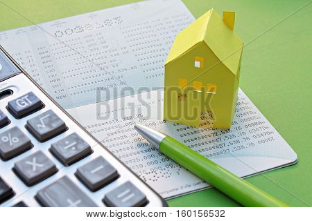 Business, finance or mortgage concept : Savings account passbook, calculator, pen and yellow paper house on green background