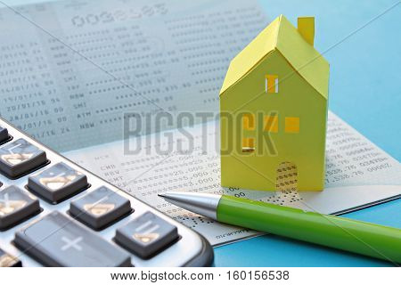 Business, finance or mortgage concept : Savings account passbook, calculator, pen and yellow paper house on blue background