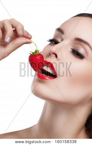 Beautiful Young Woman Eating A Strawberry. Portrait Of A Girl Close-up.