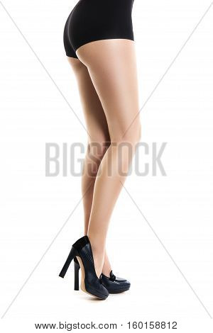 Slender Beautiful Female Feet. Woman In Black Shorts And Black Shoes With A Heel. Isolation On White