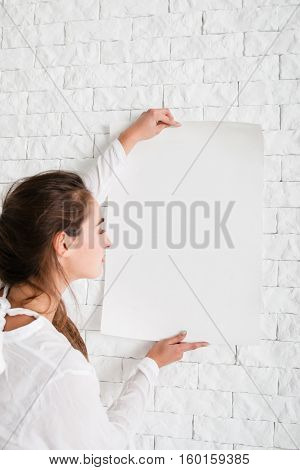 Woman holding empty whatman at wall mockup. Profile of young lady, looking at white sheet of paper, free space for advertisement or text. Warning message background
