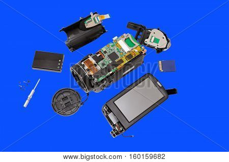 Disassembled compact camcorder. Close-up. Isolated on a blue background.