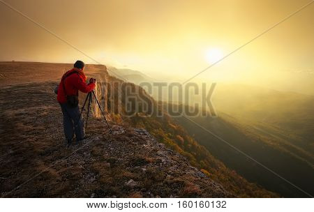 Professional on mountain. Nature photographer takes photos with mirror camera on peak of rock. Dreamy fogy landscape spring orange misty sunrise in a beautiful valley below.