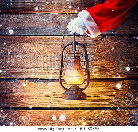 Santa Claus hand holding vintage oil lamp over Christmas holiday wooden rural background with snow. Beautiful Empty Christmas room. New Year Background. Search, searching concept.