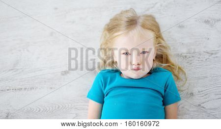 Angry Girl Lying On White Wooden Floor