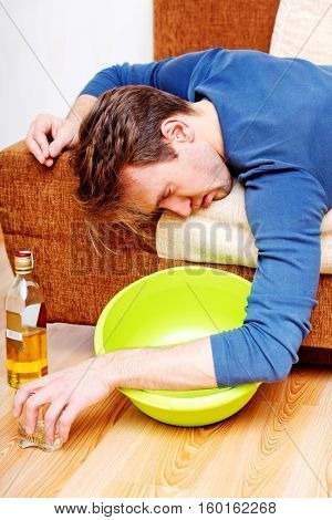 Drunk man sleeping on couch with whikey bottle and bowl