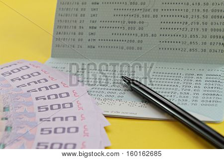 Business, finance or savings concept : Savings account passbook, Thai money baht and pen on yellow background