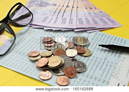 Business, finance or savings concept : Savings account passbook, Thai money baht, coins, glasses and pen on yellow background