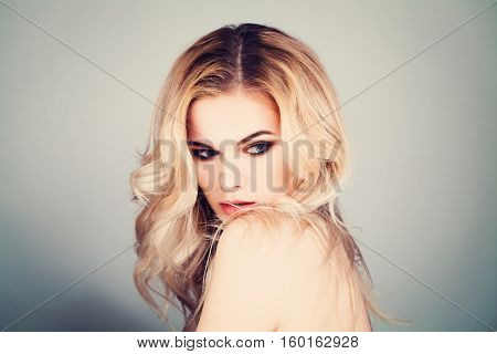 Young Sexy Model with Blonde Hair Looking Down. Beautiful Woman with Makeup and Curly Hairstyle