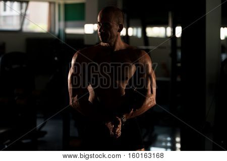Fitness Shaped Muscle Man Posing In Dark Gym