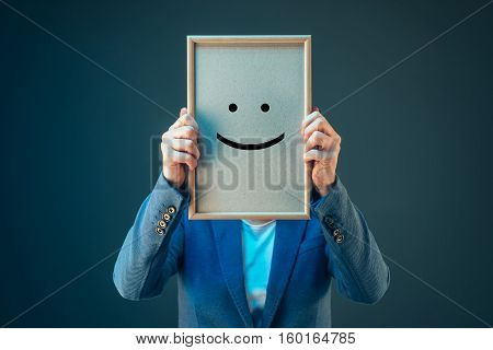 Businesswoman is optimistic about her future in corporate business holding printed happy smiley emoticon over her face