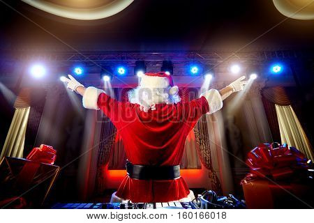 Dj Santa Claus for Christmas in the rays of light with music at the event is back put his hands up.