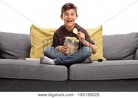 Cheerful boy sitting on a sofa and eating potato chips isolated on white background