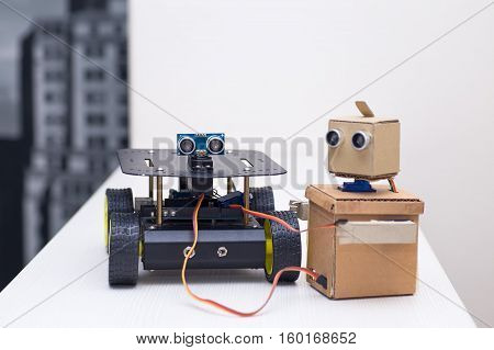 two robots stand beside on a light table