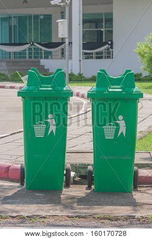 Large green wheelie bin at public park.
