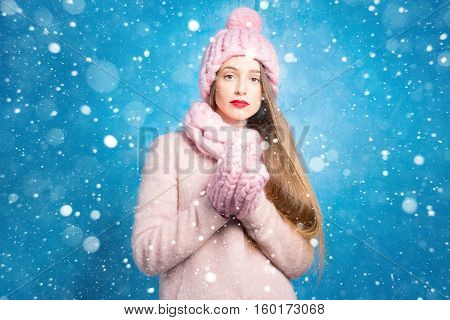 Winter portrait of a sad woman in knitted pink scurf, gloves and hat on the blue background during the snowfall poster