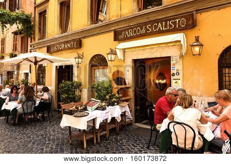 Rome Italy - May 27 2016: Unidentified people eating traditional italian food in outdoor restaurant in Trastevere district in Rome Italy.