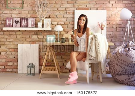 Happy woman sitting on chair, holding mobilephone, smiling at vintage home, looking at camera.
