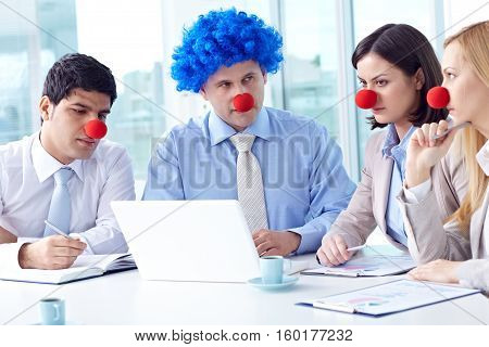 Colleagues sitting at meeting with clown s noses on their faces