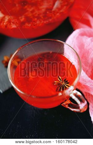 Cranberry herbal hot tea drink in glass teapot with cinnamon and star anise spice on black backdrop