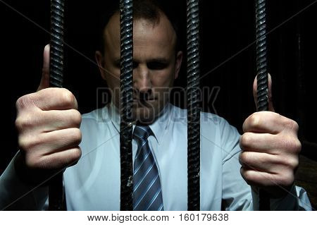 Portrait of businessman behind the bars in jail